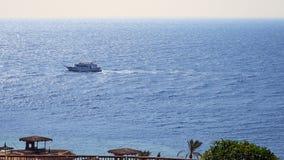 Powerboats och skepp s seglar längs det tropiska havet Arkivfoton