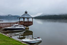 Powerboats at the pier with a gazebo and fog on Lake Teletskoye, Altai, Russia.  stock image
