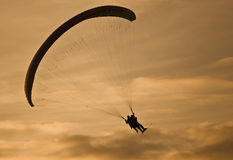 Powered parachute at sunset. Two people silhouetted midair with powered parachute or paraplane at sunset Royalty Free Stock Photos