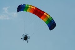 Powered Paraglider. A pilot enjoys the freedom of a powered paraglider with a rainbow-colored parachute Stock Photography