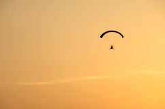 Powered paraglider flying away with sunrise Stock Image