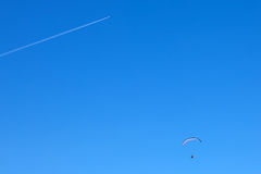 Powered paragliding with a flying plane Stock Images