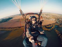 Powered paragliding tandem flight. Man taking selfie with action camera royalty free stock image