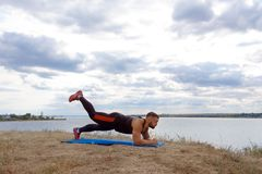 A powerful athlete with stubble and a tattoo on a shoulder standing in a plank on a natural blurred background. Stock Photos