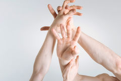 Powerful athletes hands demonstrating aggression in the studio. Hands in details. Flexible strong powerful athletes hands locating in the white colored studio Stock Photography