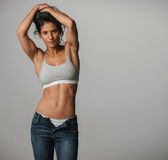 Powerful athletic woman poses with arms above her Royalty Free Stock Photos
