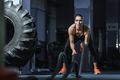 Powerful attractive muscular CrossFit trainer do battle workout with ropes. Concept: power, strength, healthy lifestyle, sport. Powerful attractive muscular Royalty Free Stock Photo