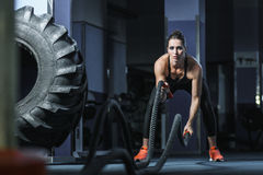 Powerful attractive muscular CrossFit trainer do battle workout with ropes. Concept: power, strength, healthy lifestyle, sport. Powerful attractive muscular Stock Image