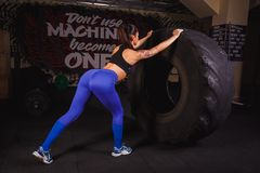 Powerful, attractive muscular girl engaged in crossfit, training with giant tires in the gym. royalty free stock photo