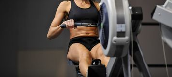 Powerful attractive muscular woman CrossFit trainer do workout on indoor rower at the gym royalty free stock photo