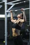 Powerful attractive woman CrossFit trainer do pull ups during workout Stock Photos