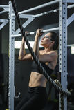 Powerful attractive woman CrossFit trainer do pull ups during workout Royalty Free Stock Image