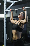 Powerful attractive woman CrossFit trainer do pull ups during workout Stock Photo