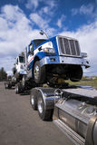 Powerful big rig semi truck carries in coupling another semi trucks different models stock images