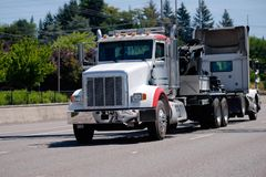 Big rig semi truck towing broken another semi truck. A powerful big rig semi truck tractor tows a broken semi truck on a highway with green trees to the repair Royalty Free Stock Photo