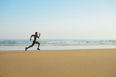 Powerful black man running by the sea Royalty Free Stock Photography