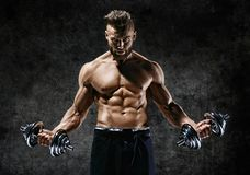 Powerful bodybuilder doing the exercises with dumbbells. Photo of strong male with naked torso on dark background. Strength and motivation Royalty Free Stock Photos