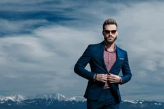 Powerful businessman closing his jacket`s buttons. And looking forward while wearing sunglasses and blue suit, standing on outdoor background stock photography