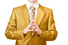 Powerful businessman folds hands together. Businessman dressed in golden suit folds hands together Royalty Free Stock Photography
