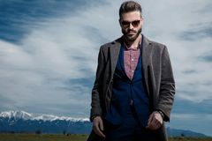 Powerful businessman posing and looking to the camera. While wearing sunglasses, a blue suit and gray coat, standing on outdoor background stock photo