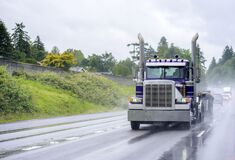 Free Powerful Classic Big Rig Blue Semi Truck With Flat Bed Semi Trailer Running On The Wet Raining Road In Front Of Another Traffic Stock Photos - 188131353
