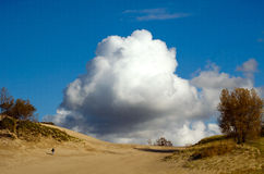 Powerful clouds and man walking up a sand dune Royalty Free Stock Photo
