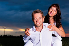 Powerful couple in front of windmill Stock Images