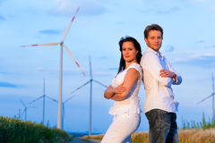 Powerful couple in front of windmill Royalty Free Stock Photo