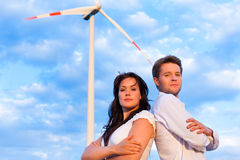 Powerful couple in front of windmill Royalty Free Stock Photos