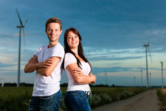 Powerful couple in front of windmill in the evenin Stock Photos