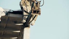 Powerful demolition machine cutting iron construction, destroying old building
