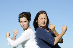 Powerful and determined female team. Two confident and determined looking attractive women standing back to back, with raised arms and fists. Clear blue sky as Stock Photo