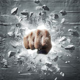 Powerful fist. Fist punching out from wall with debris Royalty Free Stock Photography