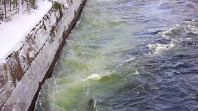 Powerful flow of water in the canal hydropower in winter. Concrete brink stock video footage