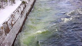 Powerful flow of water in the canal hydropower in winter. Concrete brink stock video