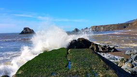 Waves crashing against the breakwall. Powerful forces of nature slamming against a man-made wall of stone Stock Images