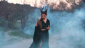Powerful and frightening girl in a green emerald long dress poses for photos in fantasy style, lady with horns on her