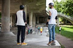 Powerful funny young guys are trained in a skate park Stock Image