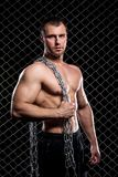 Powerful guy with a chain showing his muscles Royalty Free Stock Images