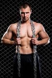 Powerful guy with a chain showing his muscles Royalty Free Stock Image