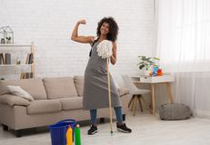 Powerful housewife holding mop and showing biceps. Powerful african-american housewife holding cleaning mop and showing biceps, housekeeping is hard work, copy royalty free stock photo