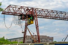 Powerful large industrial crane and cloudy weather. Powerful large industrial crane with yellow cab and cloudy weather Royalty Free Stock Photography