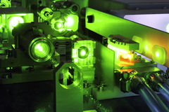 Powerful laser. Bright green laser light going inside complicate scientific system with cooling hoses inside stock photo