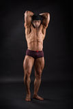 Powerful male bodybuilder showing his strong muscles. Strong bodybuilder standing against isolated background and showing his powerful muscles Royalty Free Stock Images