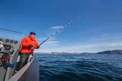 powerful man with a fishing rod in his hands. sea boat. fisherman stock images