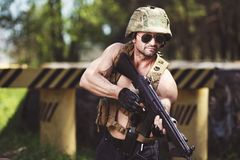 Powerful mercenary with submachine gun aiming the target near ro. Adblock. Strong ripped man in helmet and sunglasses with rifle in hand. Soldier, warrior Royalty Free Stock Photos