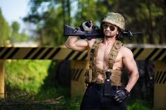 Powerful mercenary with submachine gun guarding a roadblock. Cropped portrait of strong ripped man in helmet and sunglasses with rifle in hand. Soldier Stock Images