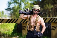 Powerful mercenary with submachine gun guarding a roadblock. Cropped portrait of strong ripped man in helmet and sunglasses with rifle in hand. Soldier Stock Photography