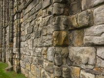 Powerful Middle Ages massive stone wall in perspective. Scotland, public places. Strong old stone wall. Middle Ages buildings in Scotland, public places, uk royalty free stock image