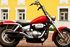 Powerful motorcycle. Strong chrome motorcycle on the background of the building Royalty Free Stock Photos